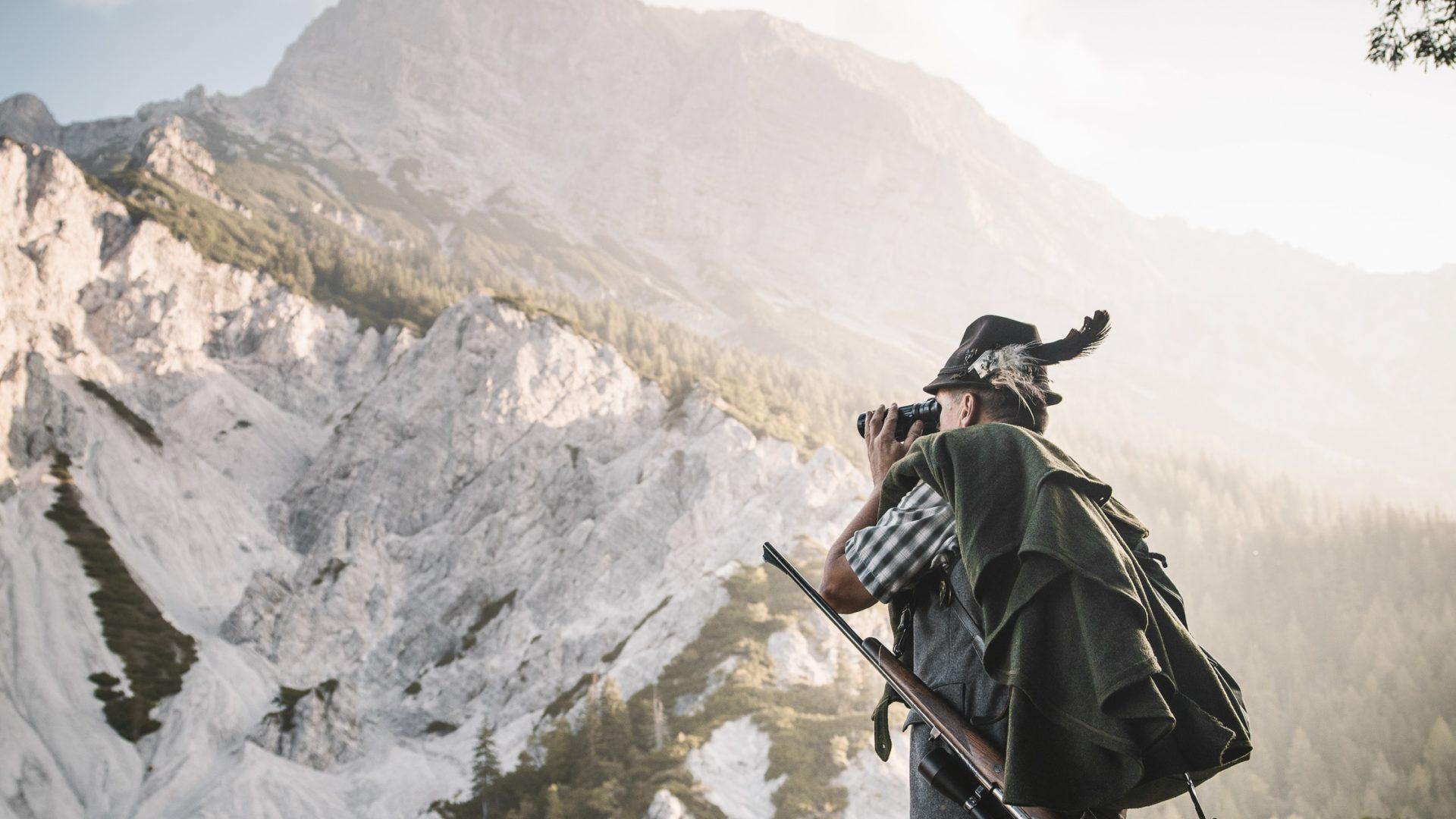 Ein Jäger im Gesaeuse beobachtet Gämsen mit dem Fernglas